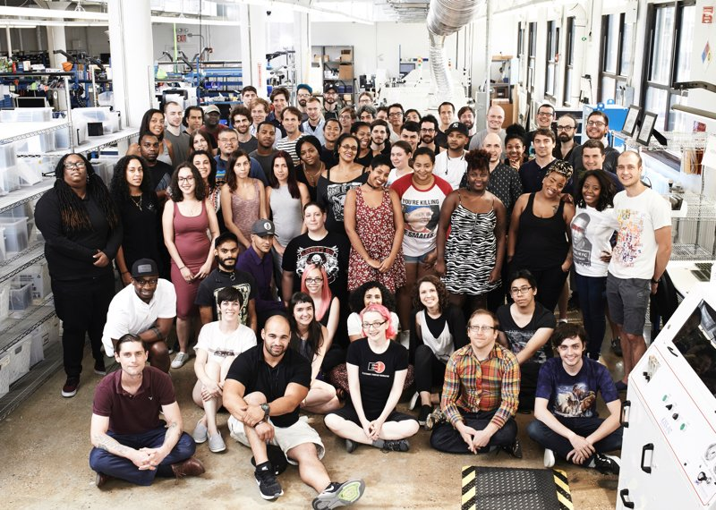 Group photo of approximately 50 people in front of manufacturing equipment