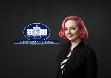 Woman with pink hair standing in front of White House Champions of Change logo