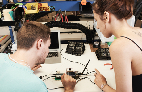 Two young individuals, backs turned, looking at electronic assembly on a worktable