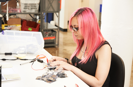 Young woman with pink hair working at an electronics workbench