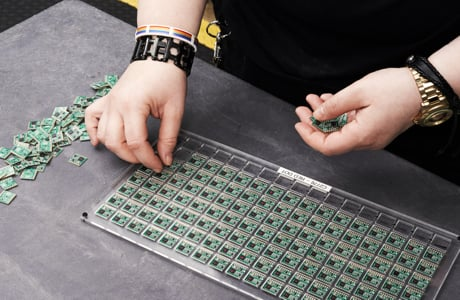 Two hands with punk bracelets assembling a grid of small electronic boards