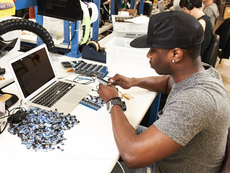 Young man with baseball cap, at electronic work bench, breaking apart a grid of small electronic boards