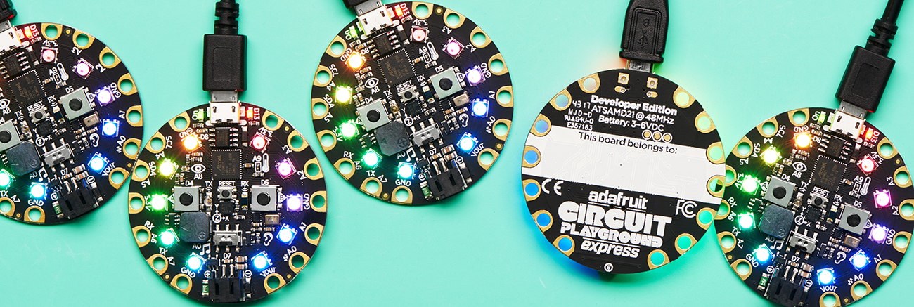 Five round circuit boards in a row, with rainbow LEDs, one is upside down and says Circuit Playground on back