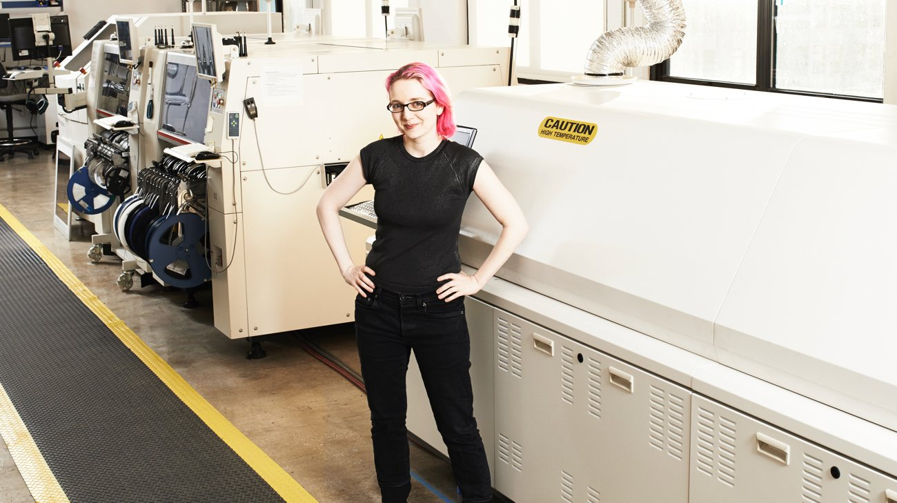 Woman with pink hair standing in front of electronic manufacturing equipment, arms akimbo.