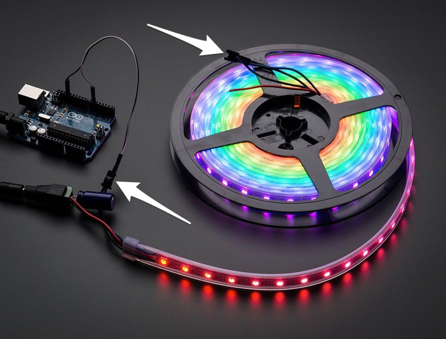 Full-length RGB LED strip in a spool, lit up in rainbow colors. Diagram arrows indicate the LED strip's built-in connectors. One at the end of the spool connects to an Arduino which is driving the strip. The other connector is at the center of the spool.